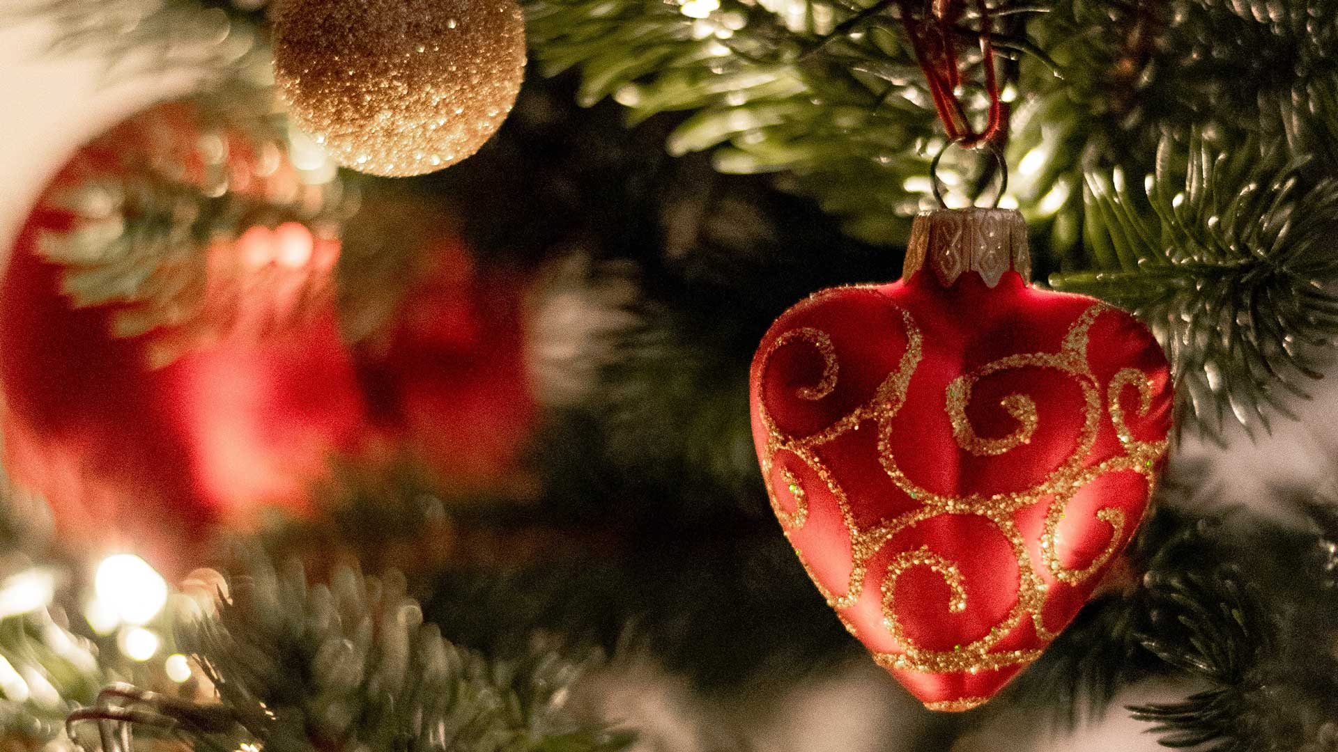 Close up image of Christmas tree with red, heart-shaped ornament in foreground