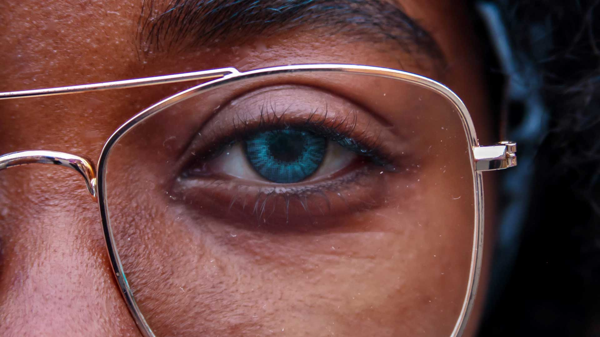 Close-up image of black man with blue eyes wearing clear metallic frame spectacles.