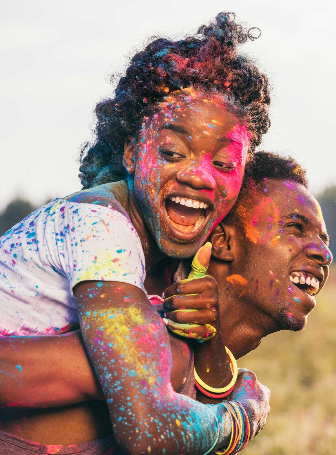 Colorful image of a young-happy African-woman with color on her face-riding on the back of a happy young african man-with paint on his face wakilisha.africa.jpg